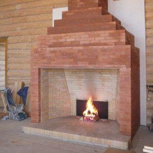 Великий цегляний камін в інтер'єрі заміського будинку: фото ідеї